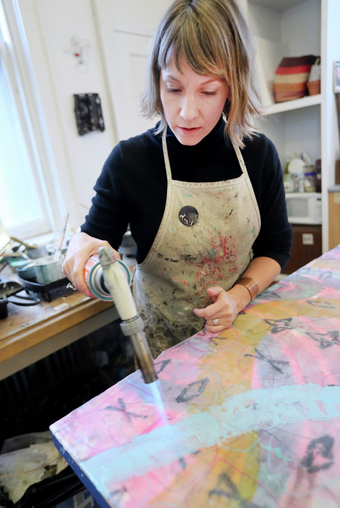 t11.8.18 Bob King -- 111718.F.DNT.ARTISTSPACESc6 -- Using a torch, Natalie Salminen blends colors on a large panel she's working on for a restaurant in Minneapolis. Bob King / rking@duluthnews.com